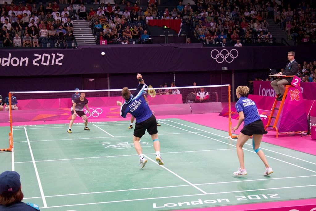 players playing doubles game in badminton court in Olympics