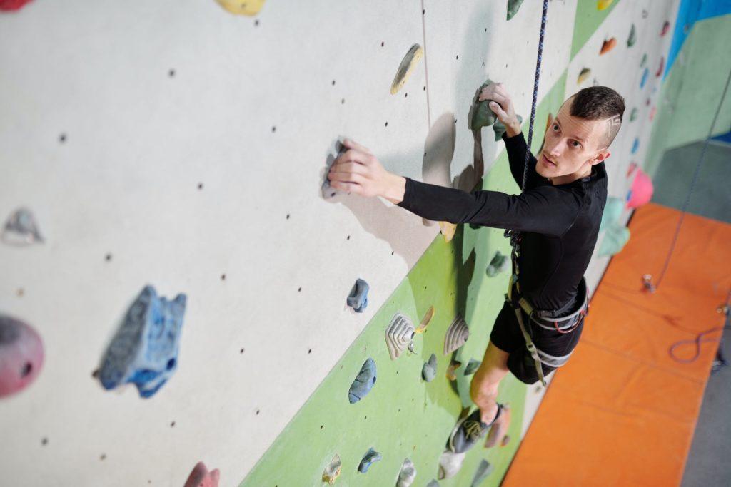 man trying indoor rock climbing
